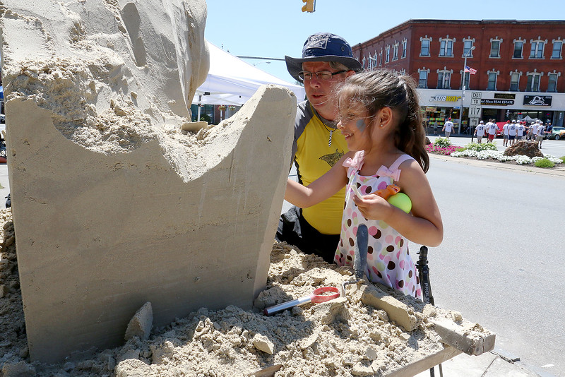Paloma Rivera, 6, got to help Sean Fitzpatrick of Saugas with his sand sculpture at the Leominster Summer Stroll in Downtown on Saturday afternoon. Rivera, from Boston, was visiting her grandmother who lives in Leominster. SENTINEL & ENTERPRISE/JOHN LOVE