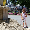Paloma Rivera, 6, watches as Sean Fitzpatrick of Saugas works on a sand sculpture at the Leominster Summer Stroll in Downtown on Saturday afternoon. Rivera, from Boston, was visiting her grandmother who lives in Leominster. SENTINEL & ENTERPRISE/JOHN LOVE
