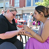 Serina Atuahene of Leominster, on left, gets her palm read by Jacklyn Tene of Leominster at the Leominster Summer Stroll in Downtown on Saturday afternoon. SENTINEL & ENTERPRISE/JOHN LOVE