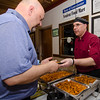 Paul Arcouette, from Venient Fast Food, serves up chicken bites during the Taste of Leominster on Wednesday evening at City Hall. SENTINEL & ENTERPRISE / Ashley Green