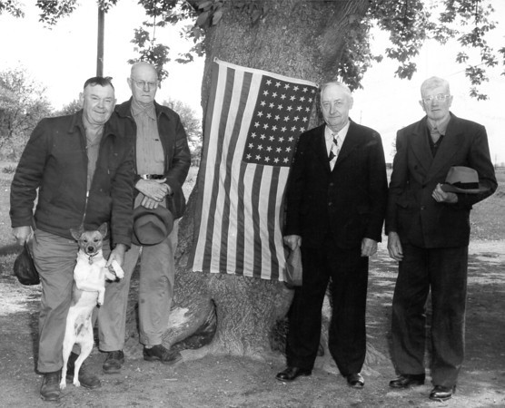 Four men, a flag and a dog pause under a shade tree in today's mystery photo. To identify those pictured, post under the photo on the Effingham Daily News Facebook page.