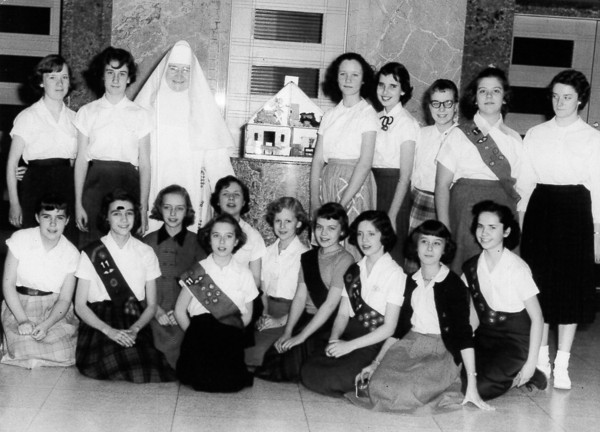A group of girls, possibly Girl Scouts, are shown with a nun and a doll house. To help identify those pictured, post under the photo at the Effingham Daily News Facebook page.