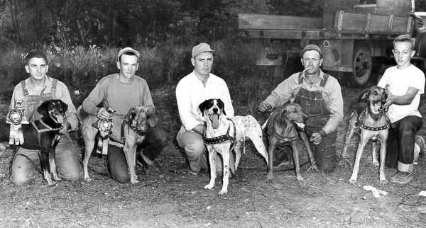 Five men with their best friends pose for a photo. This mystery photo was probably taken in the mid-20th century. Do you recognize any of the people in the photo?