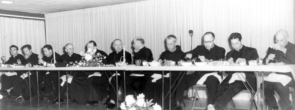 Today's mystery photo shows a group of priests gathered at a long table to share a meal.