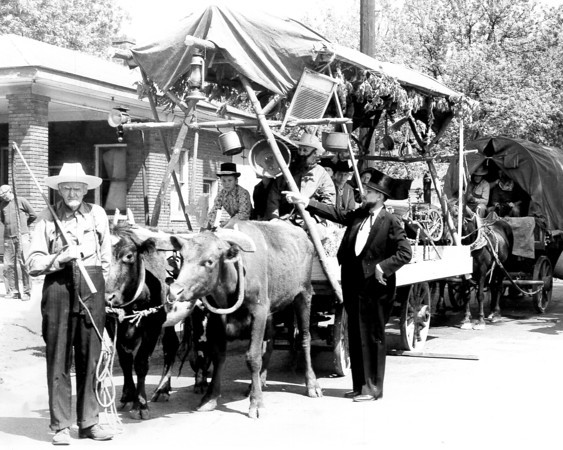 A tinker's wagon followed by a covered wagon are depicted in this photo. Were these wagons part of a centennial celebration?