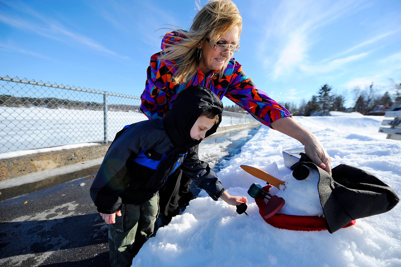 Nolan Cormier, 4, of Leominster builds a snowman with his grandmother Sue Giacomuzzi of Leominster by Lake Whalom in Lunenburg with temperatures in the 50s on Saturday.<br /> SENTINEL & ENTERPRISE / BRETT CRAWFORD