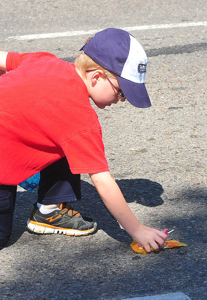 """Youngster picking up candy during the Sand & Sage Roundup Parade on Saturday. This year's theme was """"County Pride; County Wide""""."""
