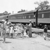 """A group of children along with several chaperones look like they are ready to hop on the train and head to parts unknown. The negative was marked """"July 1966"""". Do you recognize any of the children or adults?"""