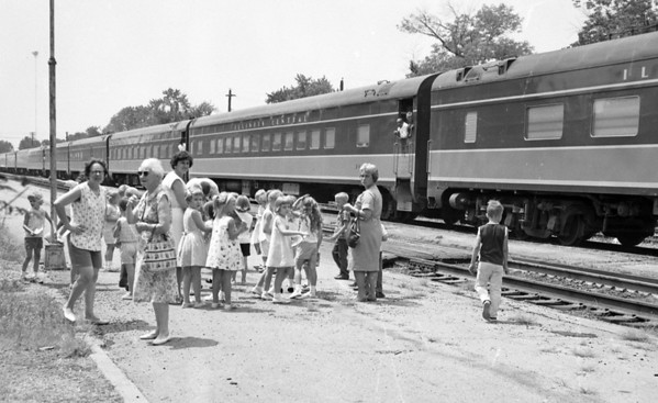 "A group of children along with several chaperones look like they are ready to hop on the train and head to parts unknown. The negative was marked ""July 1966"". Do you recognize any of the children or adults?"