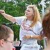 Judy Rousseau, of Fall Brook Elementary, conducts the Leominster Youth Band during Starburst at Doyle Field in Leominster on Saturday evening. SENTINEL & ENTERPRISE / Ashley Green