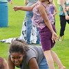 Destiney Acosta, 5, gets a lift from Amina Seale, 8, during Starburst at Doyle Field in Leominster on Saturday evening. SENTINEL & ENTERPRISE / Ashley Green
