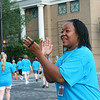 Ninth Triennial Gathering | Rhonda Pruitt, Chicago, IL, cheers on participants as they round the corner in the  Run, Walk and Roll