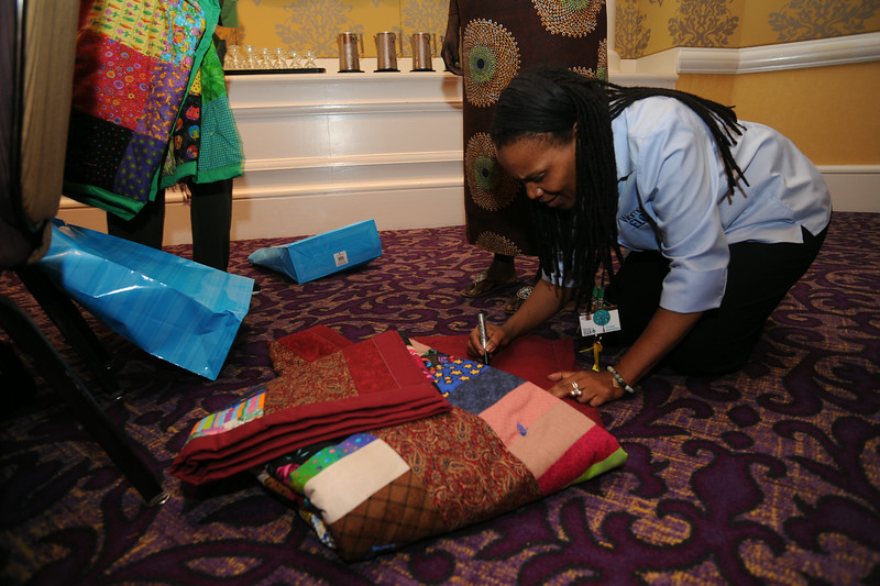 Ninth Triennial Gathering | Val Starr, director of discipleship signs a quilt that is going to an international guest.