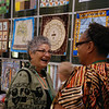 Bible study leader Diane Jacobson enjoys a conversation with a triennial participant near the wall of quilts. EH.