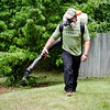 Chris Brothers, of Mosquito Squad of Central MA, sprays the backyard of a Westminster home on Wednesday afternoon. SENTINEL & ENTERPRISE / Ashley Green