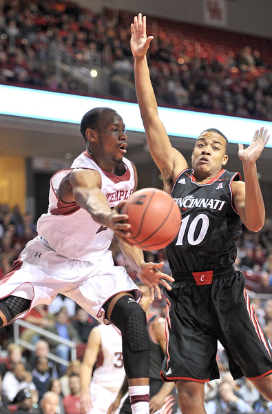 PHILADELPHIA - JANUARY 26: Temple Owls guard Will Cummings passes the basketball as he hangs in the air in an AAC game against Cincinnati January 26, 2013 in Philadelphia.