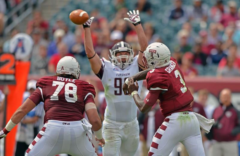 PHILADELPHIA - SEPTEMBER 14: Temple quarterback Clinton Granger (3) throws a ball around a leaping Rams defender 14, 2013 in Philadelphia.