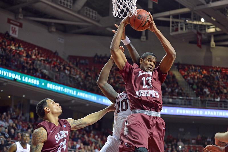 PHILADELPHIA - DECEMBER 4: Saint Joseph's Hawks forward Ronald Roberts, Jr. (13) pulls down a rebound in the Big 5 basketball game December 4, 2013 in Philadelphia.