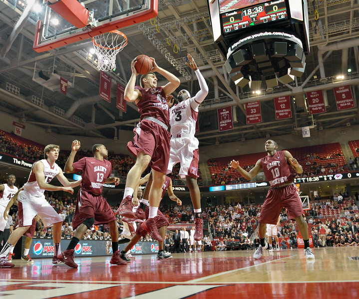PHILADELPHIA - DECEMBER 4: Saint Joseph's Hawks forward Halil Kanacevic (45) pulls down a rebound over Temple's Anthony Lee (3) in the Big 5 basketball game December 4, 2013 in Philadelphia.