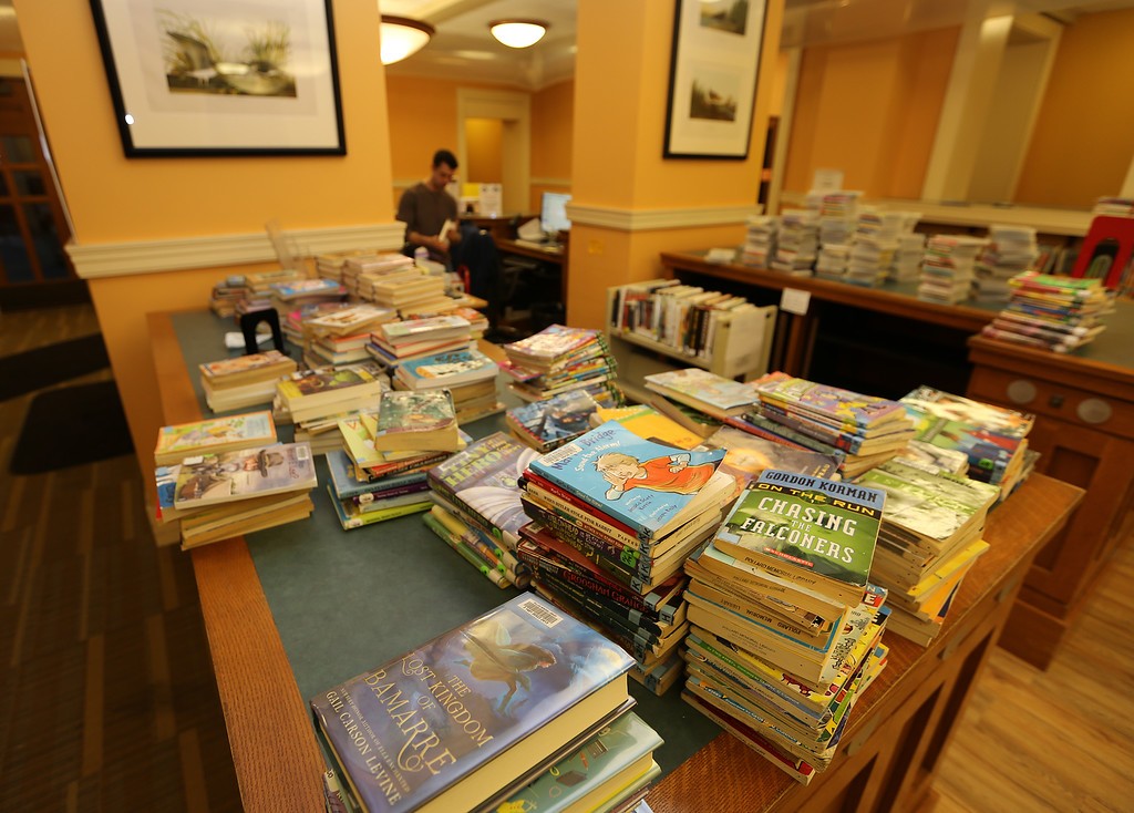 . Aftermath of flooding at Pollard Memorial Library, caused by burst pipes above the Reference Room. Flooring has been removed and some rooms are still being dried out. Children\'s books stacked near the main desk.(SUN/Julia Malakie)