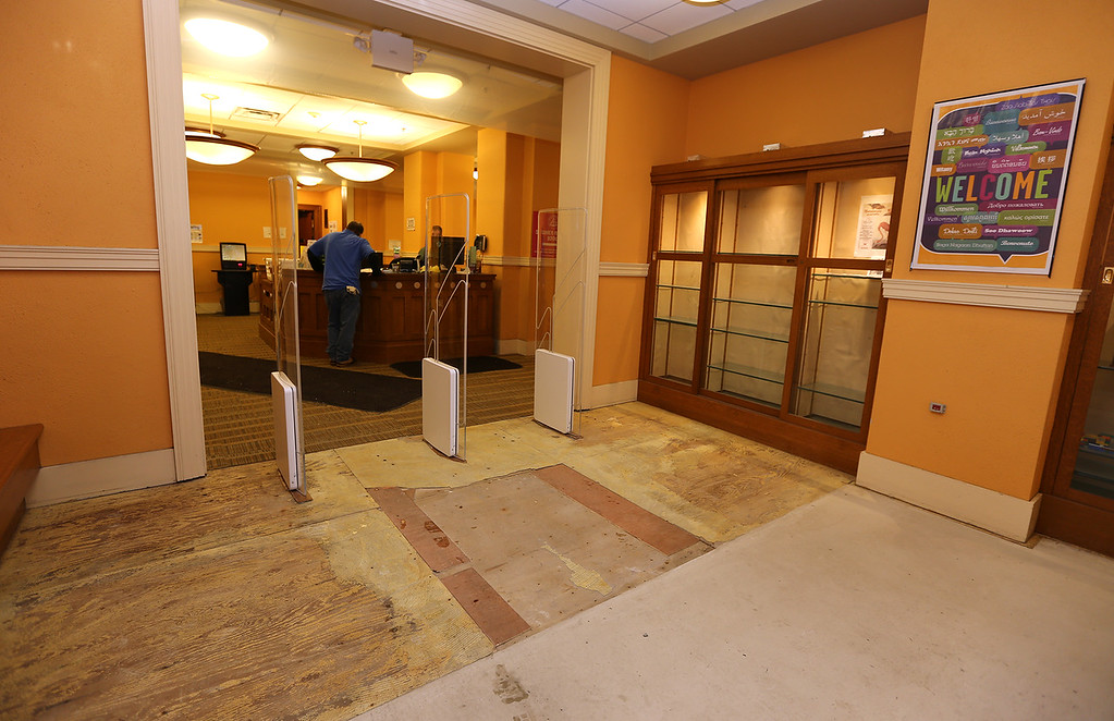 . Aftermath of flooding at Pollard Memorial Library, caused by burst pipes above the Reference Room. Flooring has been removed and some rooms are still being dried out. Entrance lobby on ground level, where flooring has been removed. (SUN/Julia Malakie)