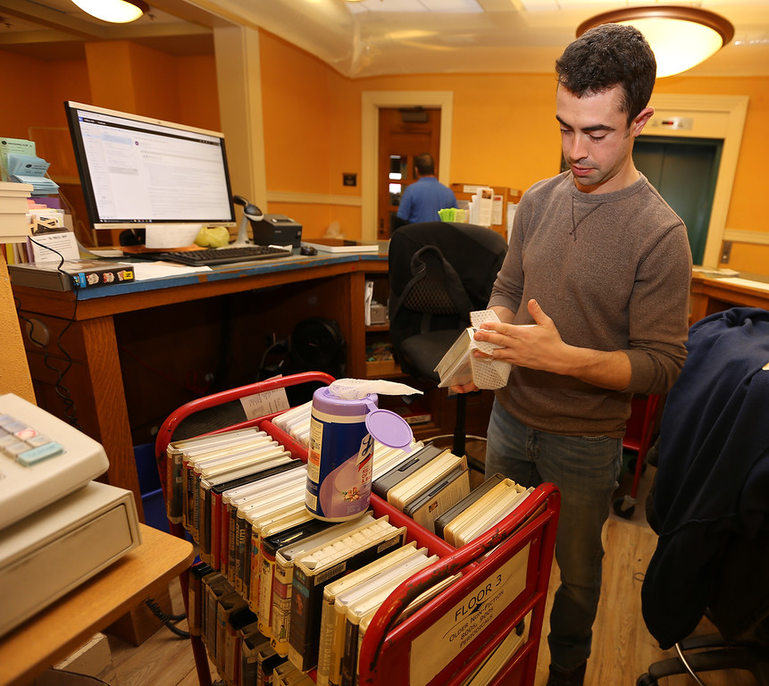 . Aftermath of flooding at Pollard Memorial Library, caused by burst pipes above the Reference Room. Flooring has been removed and some rooms are still being dried out. Library assistant Paul Regan wipes off audio books from the first floor. They were dusty before and the flood made it caked on. (SUN/Julia Malakie)