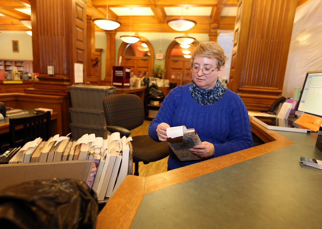 . Aftermath of flooding at Pollard Memorial Library, caused by burst pipes above the Reference Room. In the closed library, library page Maria Kelly does normal work, preparing inter-library transer requests. (SUN/Julia Malakie)