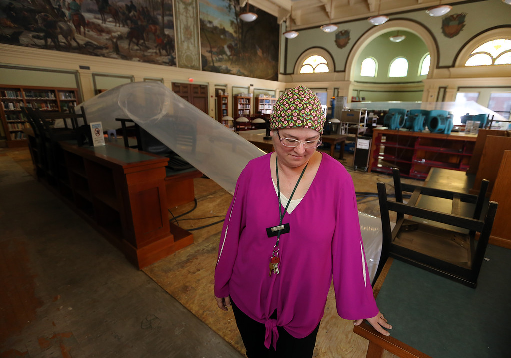 . Aftermath of flooding at Pollard Memorial Library, caused by burst pipes above the Reference Room. Library director Victoria Woodley in the Reference Room, where wood flooring has been removed, and the room is still being dried out. (SUN/Julia Malakie)
