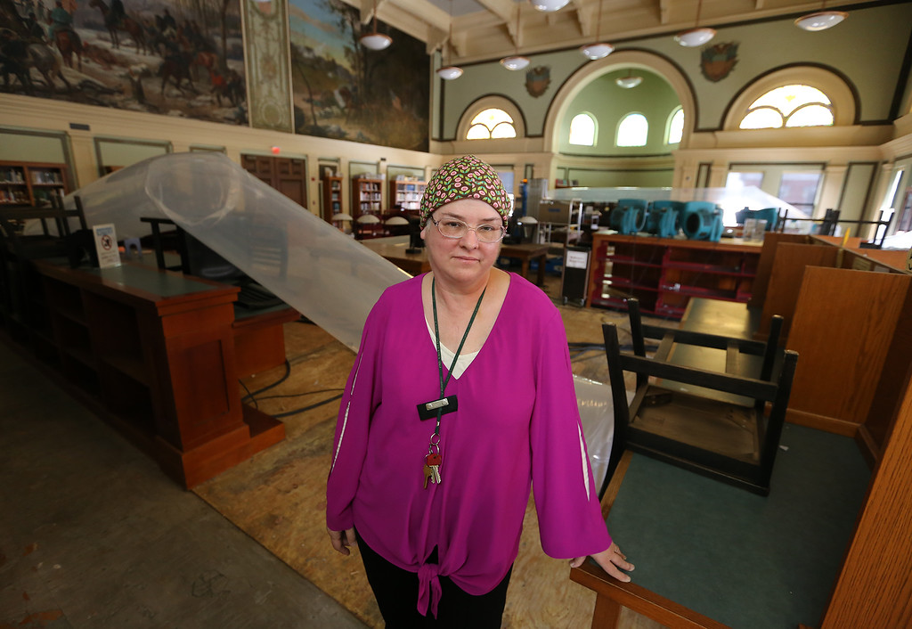 . Aftermath of flooding at Pollard Memorial Library, caused by burst pipes above the Reference Room. Library director Victoria Woodley in the Reference Room, still being dried out. Water came through the ceiling of this room. (SUN/Julia Malakie)