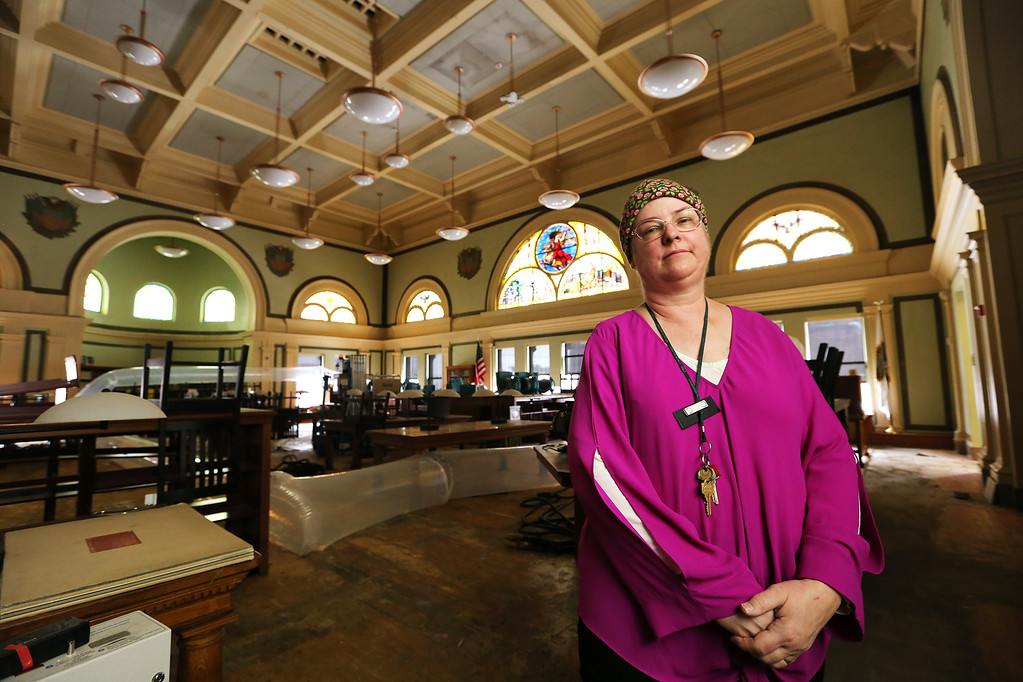 . Aftermath of flooding at Pollard Memorial Library, caused by burst pipes above the Reference Room. Library director Victoria Woodley in the Reference Room. The discolored section of ceiling at top center, is where the water came through. (SUN/Julia Malakie)