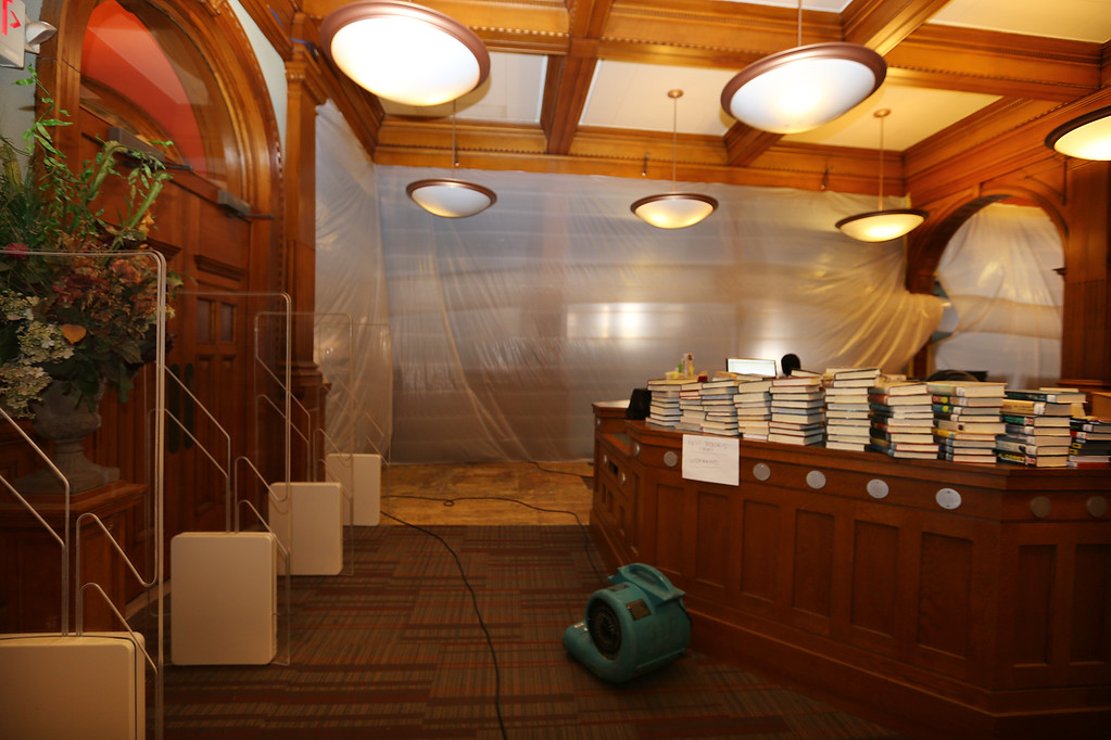 . Aftermath of flooding at Pollard Memorial Library, caused by burst pipes above the Reference Room. Flooring has been removed and some rooms are still being dried out. Books stacked at main desk. (SUN/Julia Malakie)