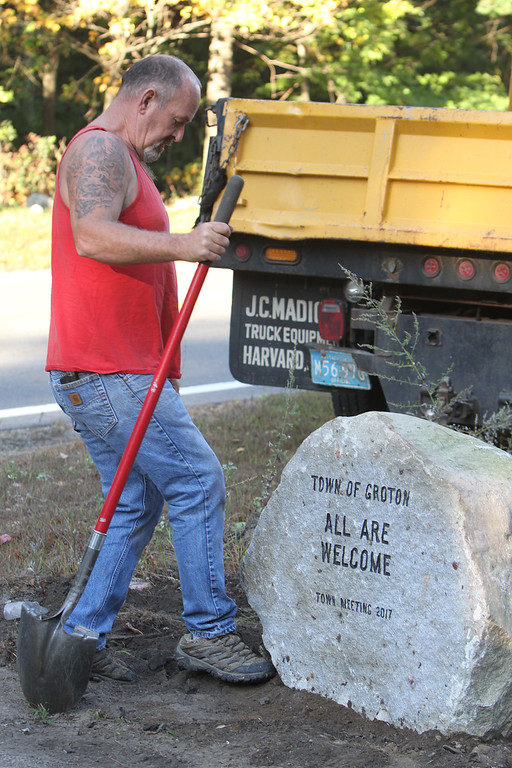 ". Installation of the ""All Are Welcome\"" stone, on Rt 119 westbound entering Groton from Littleton, sponsored by the New England Shirdi Sai Temple, the temple under construction nearby, whose entrance is next to the stone. (SUN/Julia Malakie)"