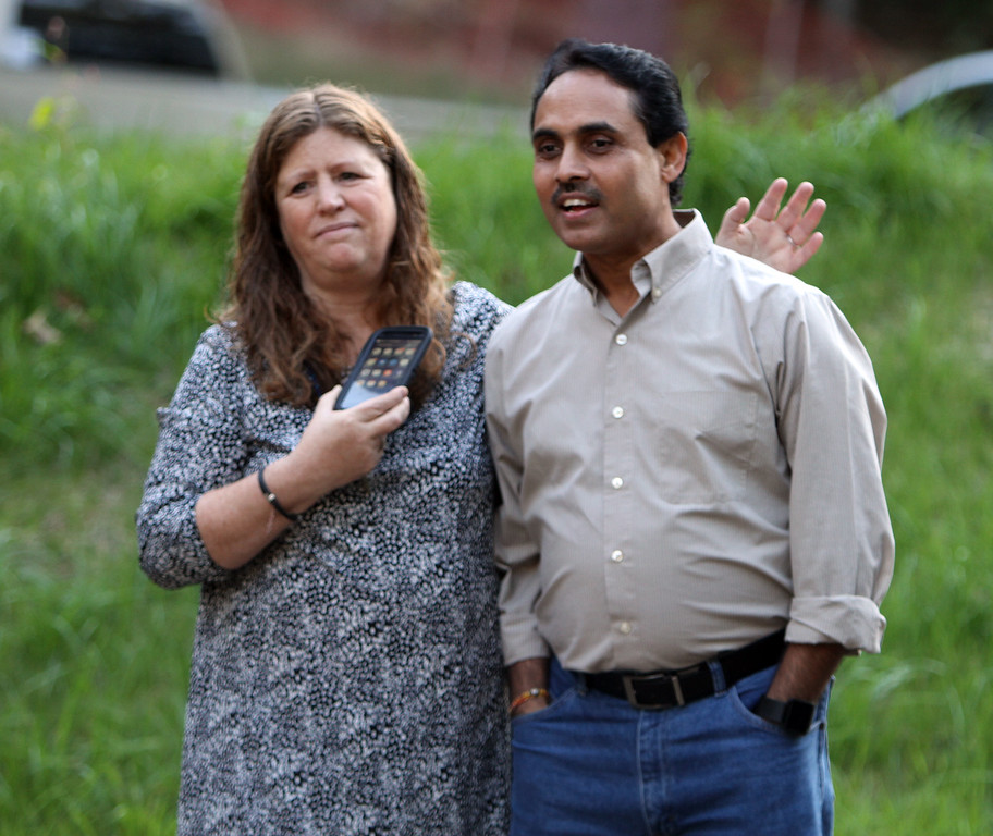 ". Neelkanth Mishra of Chelmsford, member of the temple\'s board of directors, and Amy Degen of Groton, watch the installation of the ""All Are Welcome\"" stone, on Rt 119 westbound entering Groton from Littleton, sponsored by the New England Shirdi Sai Temple, the temple under construction nearby, whose entrance is next to the stone. (SUN/Julia Malakie)"