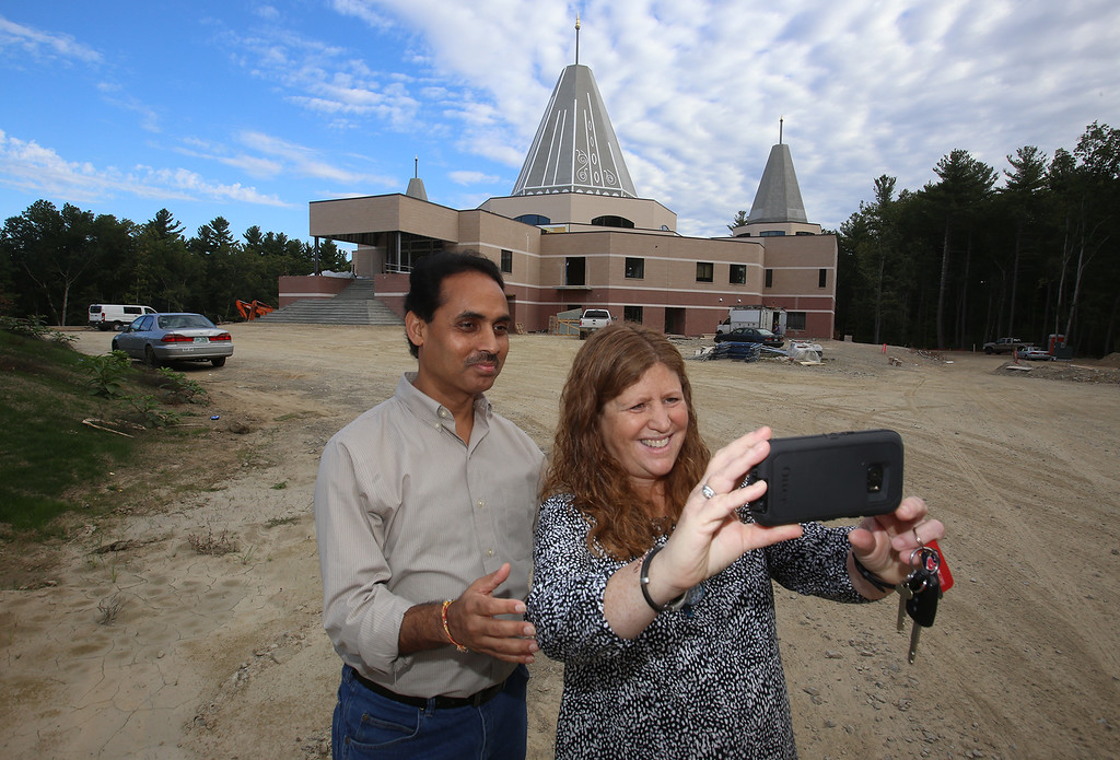 ". Installation of the ""All Are Welcome\"" stone, on Rt 119 westbound entering Groton from Littleton, sponsored by the New England Shirdi Sai Temple. Neelkanth Mishra of Chelmsford, member of the temple\'s board of directors, and Amy Degen of Groton, take a selfie at the new temple which is due to open in November. (SUN/Julia Malakie)"