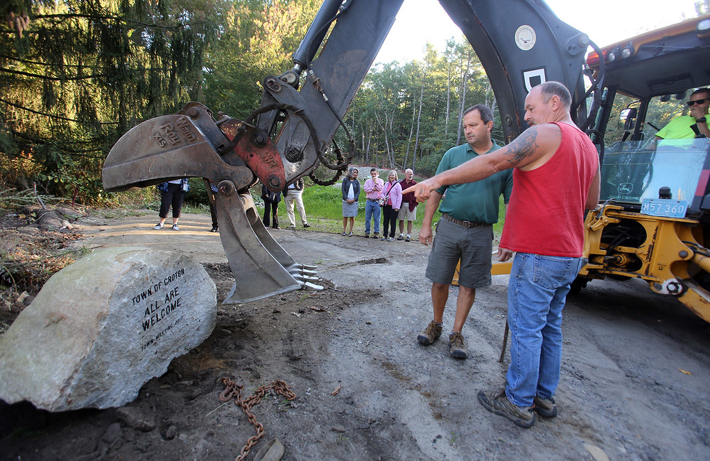 ". Groton DPW director Tom Delaney, center, supervises installation of the ""All Are Welcome\"" stone, on Rt 119 westbound entering Groton from Littleton, sponsored by the New England Shirdi Sai Temple, under construction nearby, whose entrance is next to the stone. (SUN/Julia Malakie)"