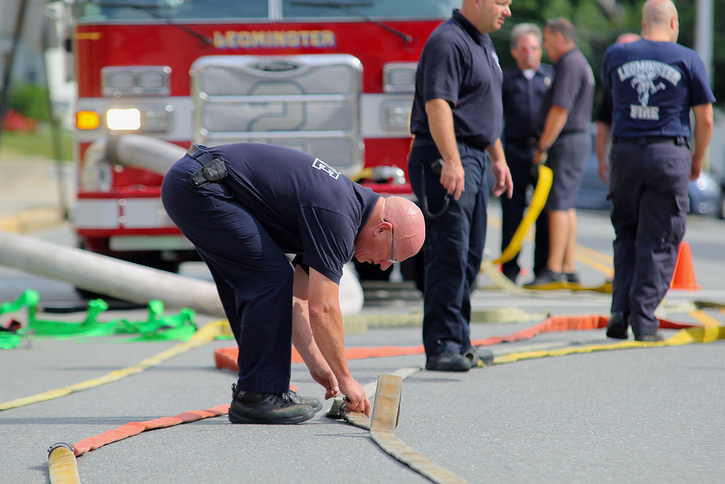 Leominster firefighter Steve Augat puts a mark on the hose so the department could see what happens as they test them on Tuesday morning in front of the Church Street station. SENTINEL & ENTERPRISE/JOHN LOVE