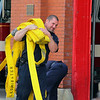Helping lay out the hoses so they can test them is firefighter Sean Gray on Tuesday morning in front of the Church Street station. SENTINEL & ENTERPRISE/JOHN LOVE