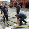 in front from left is Leominster firefighters Vinny Alia and Sean Gray as they put some hoses together so the department could test them on Tuesday morning in front of the Church Street station. SENTINEL & ENTERPRISE/JOHN LOVE