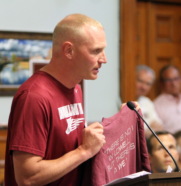"Lowell City Council listens to public comment ahead of the vote on the location for the new Lowell High School. Lowell High head coach for boys cross country and indoor track, Scott Ouellet, holds up a team shirt that says ""There is no I in Lowell, but there is a WE"" to urge unity, after speaking in support of Cawley location. (SUN/Julia Malakie)"