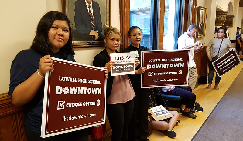 Lowell City Council listens to public comment ahead of the vote on the location for the new Lowell High School. From left, Lowell High sophomore Chhanraskmuy Chhoun, Ashley Touch, and Chhoun's mother, Susie Chhoun, all of Lowell, in hall outside the chamber. (SUN/Julia Malakie)