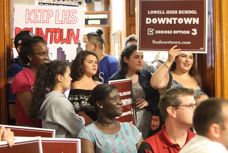 Lowell City Council listens to public comment ahead of the vote on the location for the new Lowell High School. Downtown supporters, 10th grader Yonnien Zolu, seated, center, and Greta Wilensky '16, right, holding sign. (SUN/Julia Malakie)