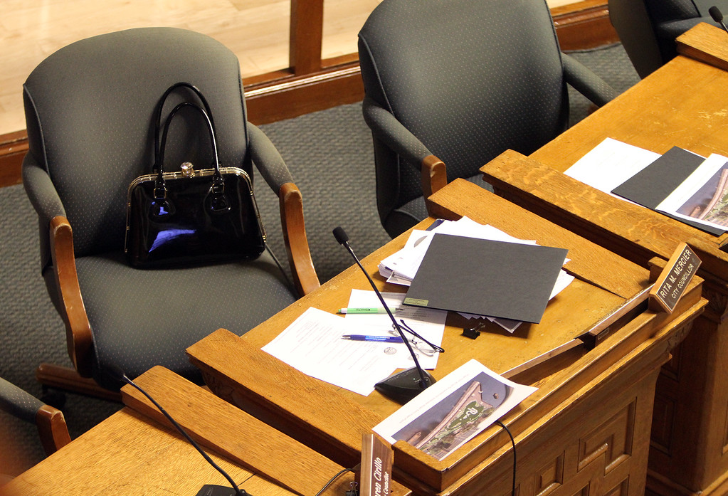 . Before start of Lowell City Council meeting, Rita Mercier saved the seat of absent Dave Conway, instead of sitting in her usual seat in alphabetical order, between John Leahy and Jim Milinazzo. (SUN/Julia Malakie)