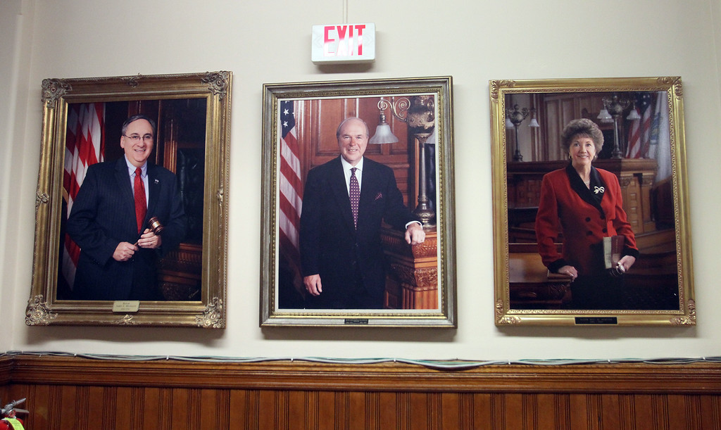 . At Lowell City Council, Rita Mercier sat in the seat of absent Dave Conway, instead of sitting in her usual seat in alphabetical order, between John Leahy and Jim Milinazzo. Mercier and Milinazzo are both former mayors, with their portraits outside the chamber. (SUN/Julia Malakie)