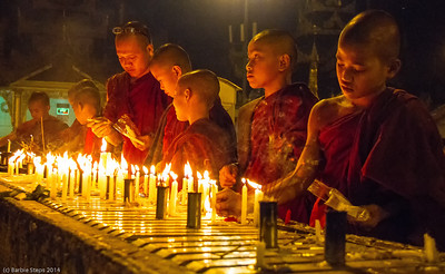 Young monks lighting candles at Schwedegon Padagon in Yangoon