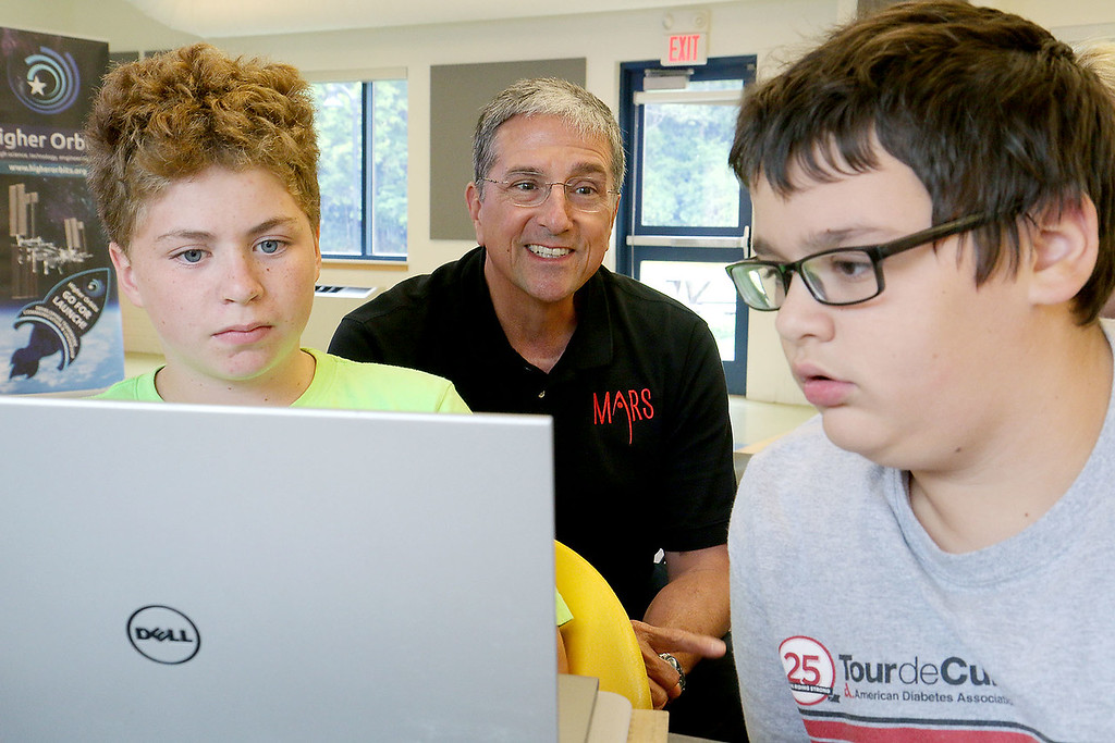 . Former NASA astronaut Don Thomas listens to some ideas from Jalen Leider, 13, of Fitchburg and Logan McGarry, 12, of Gardner as they explains some of the ideas that their group came up with for experiments in space at the Boys and Girls Club this week. SENTINEL & ENTERPRISE/JOHN LOVE