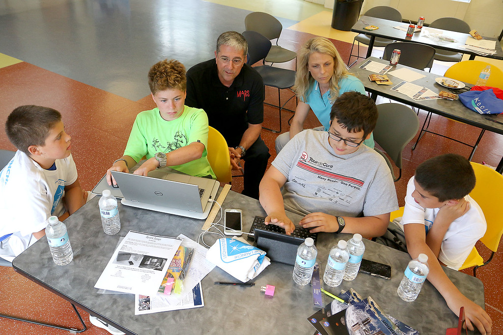. From left is Jacob Tocci, 12, from Leominster Jalen Leider, 13, of Fitchburg, Logan McGarry, 12, of Gardner and Jeff Tocci, 13, of Leominster as they explain the ideas they have for an experiment in space with former NASA astronaut Don Thomas and Michelle Lucas the President and founder of Higher Orbits. The two of the brought that program to the Leomister/Fitchburg Boys and Girls Club for three days this week. SENTINEL & ENTERPRISE/JOHN LOVE