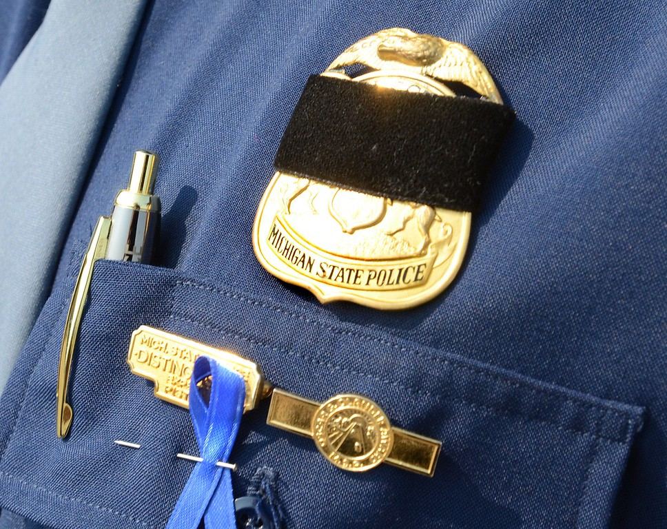. A black ban over the badge of Michigan State trooper at the funeral of Michigan State trooper Chad Wolf, 38 of Fenton, a motorcycle trooper was hit and dragged northbound on  I-75 in Independence Township Friday, later dying from his injuries.  Tuesday, September 1, 2015.  Tim Thompson-The Oakland Press