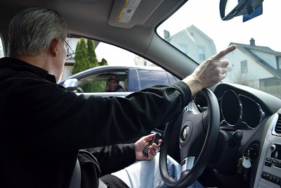 Dayne Thomas, co-chair of the General Motors Modern Housing Steering Committee, is stopped on the side of the road by a man interested in purchasing a home in the General Motors Modern Housing neighborhood in Pontiac, near General Motor's global propulsion systems facility on Glenwood Avenue, on Friday, April 14, 2017.
