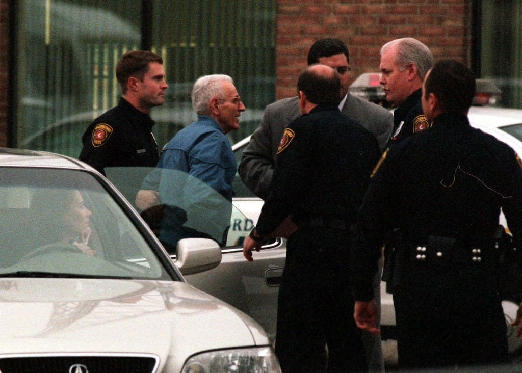 . Jack Kevorkian is escorted to the police station in Waterford Township by police officers for his arraignment Wednesday after turning himself in.