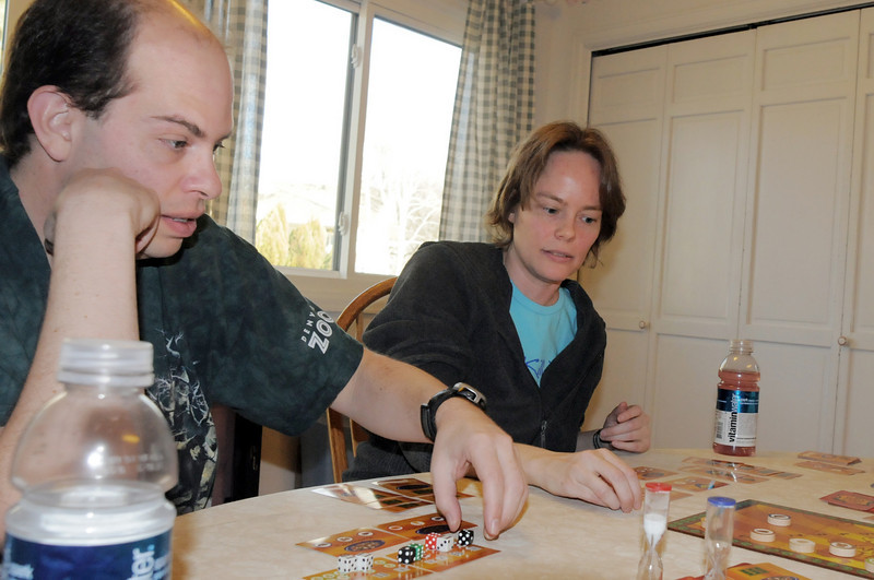 BE0127game10<br /> Brian Modreski, left, prepares to move dice as Lisa Bjornseth watches while playing Wok Star at the 104th gaming event by Time Well Spent Games at Dave Jones home in Eagle Trace on Saturday. <br /> <br /> January 22, 2011<br /> staff photo/David R. Jennings